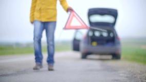 Il maschio con il suo automobile ripartita con le luci di rischio ha messo il triangolo riflettente dell'indicatore di emergenza video d archivio