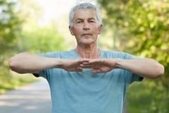 Il maschio dai capelli grigio sicuro allunga le mani, fa l'esercizio fisico o l'allenamento in aria aperta, ha espressione faccia Fotografia Stock