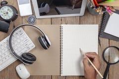 Il maschio della mano di affari scrive la matita sulla nota di Libro Bianco e sugli oggetti business, posto di lavoro di affari immagine stock libera da diritti