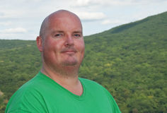 Il maschio di peso eccessivo dopo fa un'escursione in su una montagna della foresta Immagine Stock