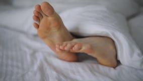 Il maschio di riscaldamento paga a letto sotto la coperta video d archivio