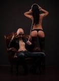 Il maschio DJ si siede nella sedia del lether e nella donna nuda delle tenute che stanno indietro il lato dalle cuffie Fotografia Stock Libera da Diritti
