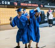Il maschio e gli anziani di laurea femminili della High School urtano le anche per celebrare i diplomi Immagini Stock Libere da Diritti