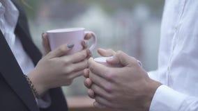 Il maschio e le mani femminili tengono le tazze di coffe in loro maschio del primo piano delle mani all'aperto e mani femminili c stock footage