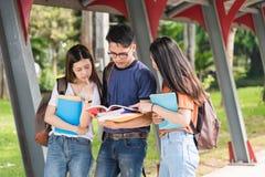 Il maschio e le studentesse stanno sui libri e sui computer portatili sopra Immagini Stock