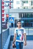 Il maschio ha vestito con indifferenza il turista barbuto con uno zaino che sta sulla vecchia via della città con la retro macchi fotografie stock libere da diritti