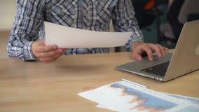 Il maschio lavora con il foglio elettronico stampato immagine stock