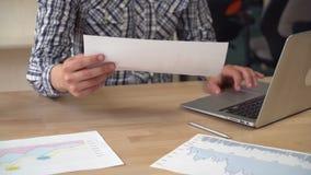 Il maschio lavora con il foglio elettronico stampato stock footage
