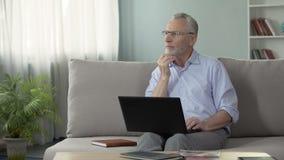 Il maschio nel suo 50s che si siede sullo strato e che lavora al computer portatile, freelance e professione archivi video