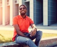 Il maschio nero sorridente si è vestito in una camicia di polo rossa Fotografia Stock