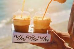 Il maschio passa il caffè del frappe del ghiaccio della tenuta due sulla spiaggia vicino al mare Enjoyng del giovane durante la v Fotografia Stock