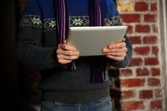 Il maschio passa il computer della compressa della tenuta vicino al muro di mattoni Fotografie Stock