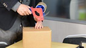 Il maschio passa il contenitore di imballaggio con nastro adesivo di condotta autoadesivo stock footage