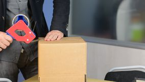 Il maschio passa il contenitore di imballaggio con nastro adesivo di condotta autoadesivo video d archivio