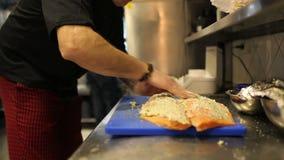Il maschio passa il cuoco unico che lubrifica il filetto di pesce rosso video d archivio