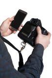 Il maschio passa la macchina fotografica digitale ed il telefono cellulare della tenuta Fotografia Stock Libera da Diritti