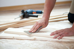 Il maschio passa la plancia di legno di lucidatura Fotografie Stock