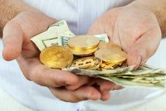 Il maschio passa le fatture di soldi della tenuta e le monete dei bitcoins Fotografia Stock Libera da Diritti