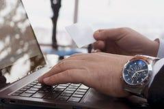 Il maschio passa le tastiere della carta di credito e del computer portatile della tenuta Immagini Stock