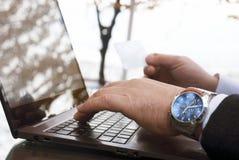 Il maschio passa le tastiere della carta di credito e del computer portatile della tenuta Fotografia Stock Libera da Diritti