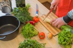 Il maschio passa le verdure di taglio sulla lavagna della cucina Alimento sano Equipaggi la preparazione delle verdure, cucinanti Fotografie Stock Libere da Diritti