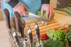 Il maschio passa le verdure di taglio sulla lavagna della cucina Alimento sano Equipaggi la preparazione delle verdure, cucinanti Immagini Stock