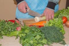 Il ` maschio s passa la cottura del pasto sano nella cucina, dietro gli ortaggi freschi Alimento sano Immagine potata delle verdu Fotografia Stock