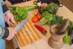 Il ` maschio s passa la cottura del pasto sano nella cucina, dietro gli ortaggi freschi Alimento sano Immagine potata delle verdu Immagine Stock Libera da Diritti