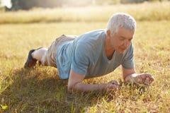 Il maschio senior fa per spingere aumenta o la plancia su erba verde, ha allenamento all'aperto, ha ente flessibile nella vecchia Immagini Stock Libere da Diritti