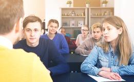 Il maschio serio e le studentesse che seguono le spiegazioni di insegnano a Fotografia Stock Libera da Diritti