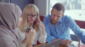 Il maschio tre ed i soci commerciali femminili sono comunicanti e beventi il tè archivi video