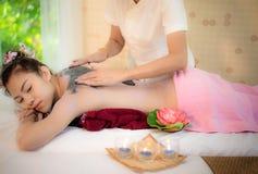 Il massaggiatore che fa la stazione termale di massaggio con il fango del trattamento sull'ente asiatico della donna nello stile  Immagine Stock
