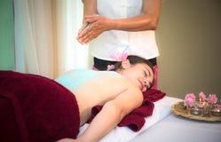 Il massaggiatore che fa la stazione termale di massaggio con lo zucchero del trattamento sfrega sull'ente asiatico della donna ne Immagini Stock Libere da Diritti