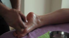 Il massaggiatore con aiuto di olio e della pietra fa il massaggio del piede stock footage