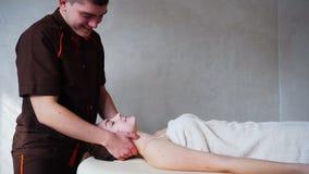 Il massaggiatore del tipo con le forti mani impasta il collo della ragazza, che si trova sullo strato nella stanza luminosa di co archivi video