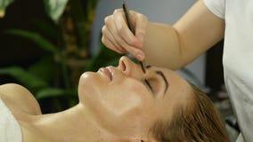 Il massaggiatore fa l'agopressione su un fronte femminile Medicina alternativa cinese archivi video