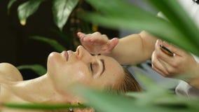 Il massaggiatore fa l'agopressione su un fronte femminile Medicina alternativa cinese 4K archivi video