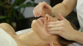 Il massaggiatore fa l'agopressione su un fronte femminile Medicina alternativa cinese Movimento lento archivi video