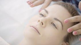 Il massaggiatore femminile rende il massaggio facciale della donna di menzogne in clinica dell'interno video d archivio