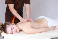 Il massaggiatore maschio professionista impasta il ` s della ragazza di nuovo al paziente, che si trova Fotografia Stock