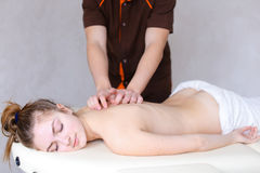 Il massaggiatore maschio professionista impasta il ` s della ragazza di nuovo al paziente, che si trova Fotografie Stock Libere da Diritti
