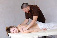 Il massaggiatore professionista del tipo impasta indietro del paziente femminile, che si trova Immagine Stock Libera da Diritti