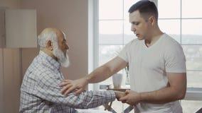 Il massaggiatore si scalda una mano dell'uomo prima del massaggio archivi video