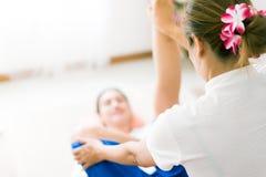 Il massaggiatore sta dando a donne un allungamento della gamba Fotografie Stock