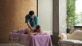 Il massaggiatore in stazione termale lussuosa incita la donna a massaggiarlo indietro archivi video
