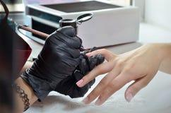 Il Master del manicure dipinge la lucidatura rosa del gel sulle unghie, sui precedenti della bottiglia e dell'essiccatore immagini stock libere da diritti