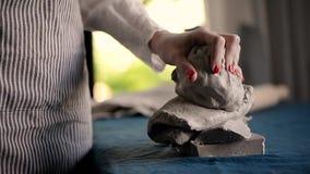 Il Master impasta il grumo di argilla sul tessuto blu della tela, tiri Argilla da modellare, fatta a mano archivi video
