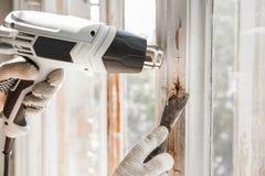 Il Master rimuove la vecchia pittura dalla finestra con la pistola e la ruspa spianatrice di calore closeup Fotografia Stock Libera da Diritti