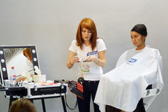 Il Master truccatore della profumeria internazionale di Intercharm Autumn Moscow XXI e di mostra dei cosmetici applica la giovane Fotografie Stock