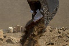 Il materiale di riempimento ed i detriti della costruzione scorrono dalla pala del carrello elevatore Immagine Stock